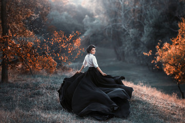 girl in black and white vintage dress is running looking around. Silk fabric skirt train waving fly in wind motion. Artistic Photography. Medieval fantasy woman walk in autumn nature, tree orange leaf