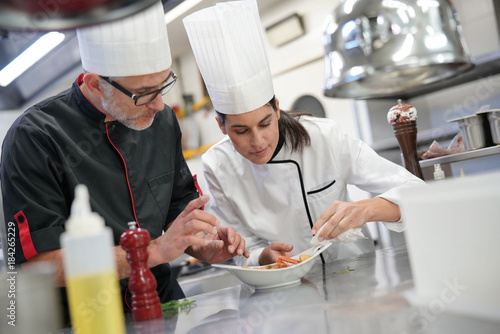 Professional cook chefs in kitchen improving dish composition Canvas