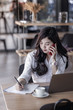 young asian business woman using smartphone and write on notebook