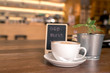 """A cup of coffee in relax time on wood table beside mini blackboard with wish text """"GOD BLESS YOU"""""""