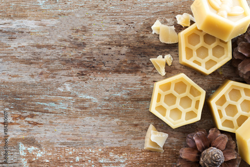 Photo natural yellow beeswax on wooden background.