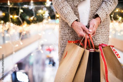 Fototapeta Senior woman with bags doing Christmas shopping. obraz