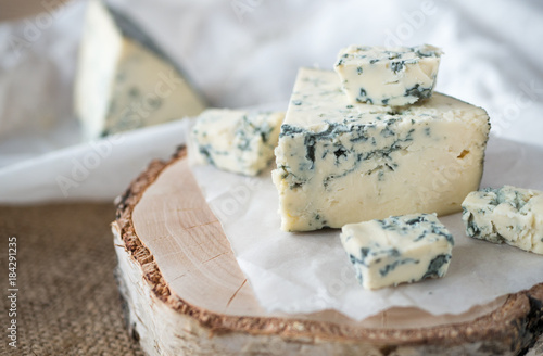 Fotografie, Tablou  Tasty blue cheese on a wooden background and burlap