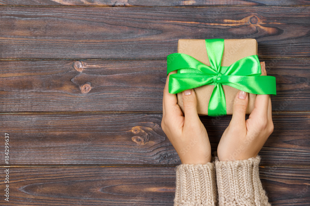 Fototapeta Woman hands give wrapped valentine or other holiday handmade present in paper with green ribbon. Present box, decoration of gift on white wooden table, top view with copy space