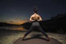 Woman Practicing Yoga Near A River