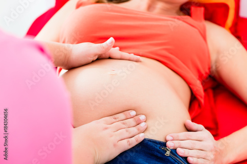 Photo Midwife exanimating belly of lying pregnant woman manually with both hands