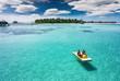 Mann und Frau auf einem Tretboot vor einer tropischen Insel auf den Malediven, Luftaufnahme
