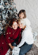 Grandmother, mother and little girl sit before a white Christmas tree