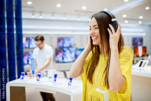 Spoed Foto op Canvas Muziekwinkel Close up of adorable attractive happy girl testing headphones in a tech store.