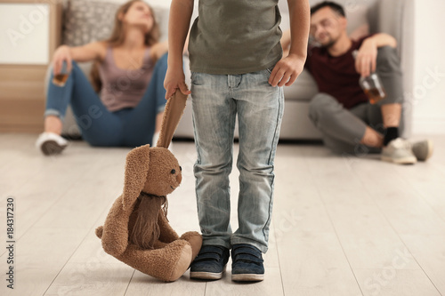 Tela Little boy holding toy bunny while his parents drinking alcohol on background