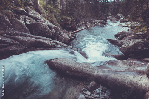 Gorgeous view the small waterfall with clear cold blue water flowing down to the wild dense woods in the Tatras Mountains in Slovakia. Artistic retouching. Long exposure effect.