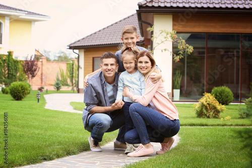 Fotografie, Obraz  Happy family in courtyard near their house