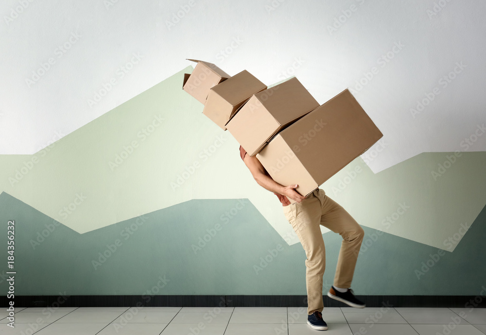 Fototapety, obrazy: Man with moving boxes near color wall