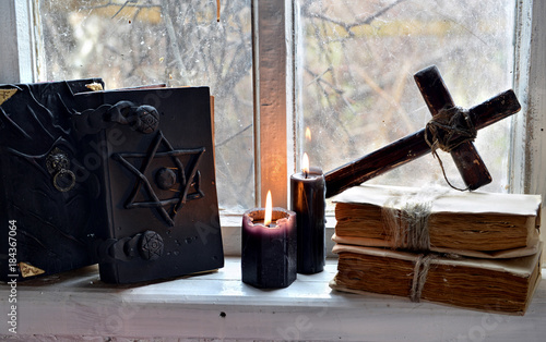 Black magic books, black candles and cross against old