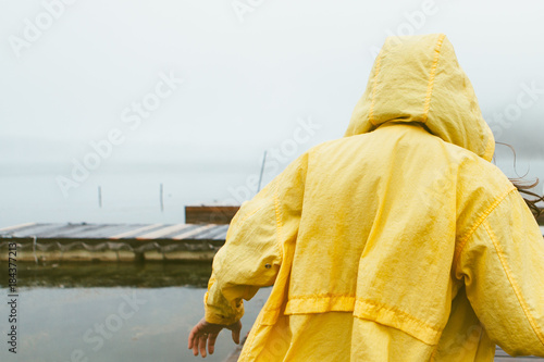 Young Woman in Yellow Raincoat on a Dock