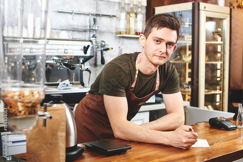 Fototapety, obrazy: The portrait of the guy baristas at workplace on background of coffee