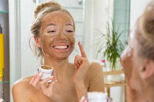 Fotografiet  Young beautiful girl applying facial scrub mask on skin
