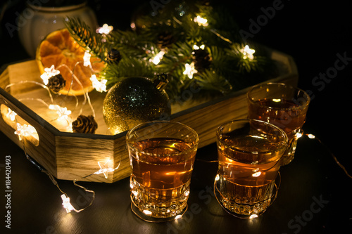 New Year Party decoration with alcohol shot glasses. Toned. Spruce tree, oranges, lights, garlands.