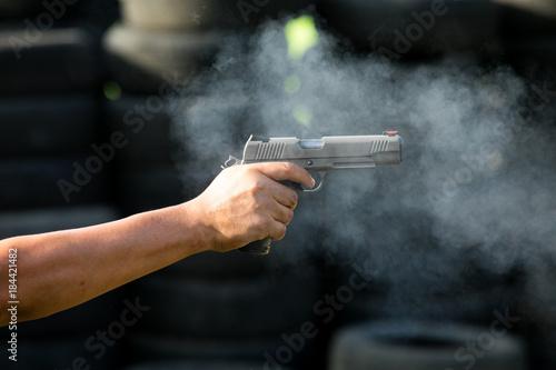 Fotografía  Man Firing Pistol at Target in Shooting Range