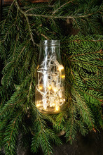 Christmas Lights Garland In Glass Bottle On Green Fir Tree Branches Over Dark Texture Background. Christmas Holiday Mood Card. Top View With Space