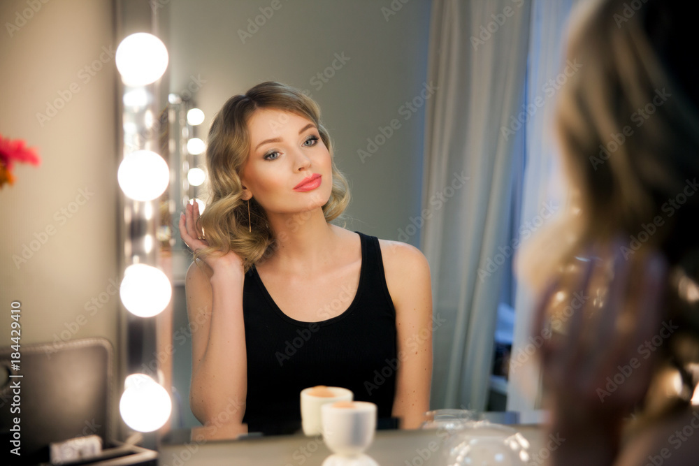 Valokuva  Attractive blonde girl primp at the mirror with lamps in the beauty studio