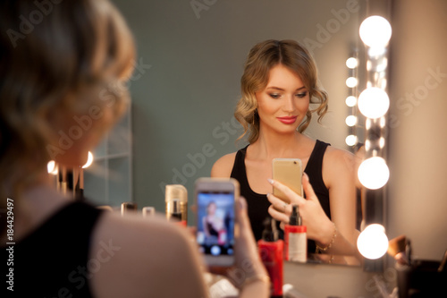 Valokuva  Attractive blonde girl take selfie with a phone at the mirror with lamps in the beauty studio