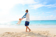 father and daugher play on tropical beach