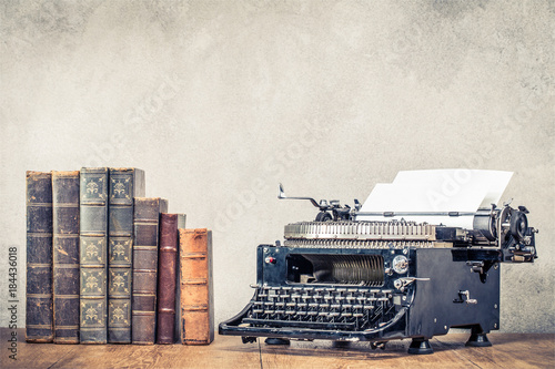 Papiers peints Retro Vintage old books and aged black typewriter with paper blank on wooden table front concrete wall background. Retro instagram style filtered photo