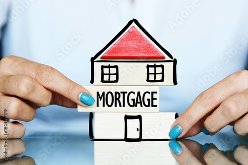 Fototapeta Release the mortgage of the property concept with young woman and house symbol on a table obraz