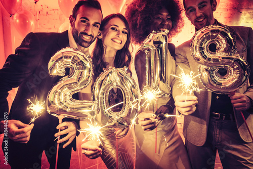 Party people women and men celebrating new years eve 2018 with sparklers and Cha Poster
