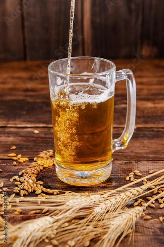 Plakat Powyżej widok ręki trzymającej szklankę piwa z pianki, z oddziału pszenicy i pszenicy na drewnianym stole