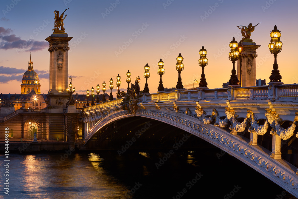 Fototapeta Pont Alexandre III Bridge and illuminated lamp posts at sunset with view of the Invalides. 7th Arrondissement, Paris, France