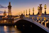 Fototapeta Paryż - Pont Alexandre III Bridge and illuminated lamp posts at sunset with view of the Invalides. 7th Arrondissement, Paris, France