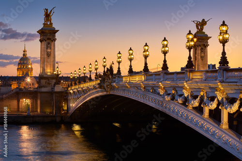 Recess Fitting Paris Pont Alexandre III Bridge and illuminated lamp posts at sunset with view of the Invalides. 7th Arrondissement, Paris, France