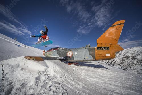 Fényképezés Snowboarding jump over plane in snowpark winter mountains