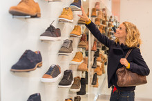 Woman Holding Shoe While Standing In Store
