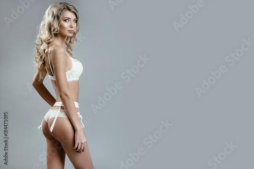 Fotografie, Obraz  Beautiful blonde girl in white lingerie posing in studio on gray background
