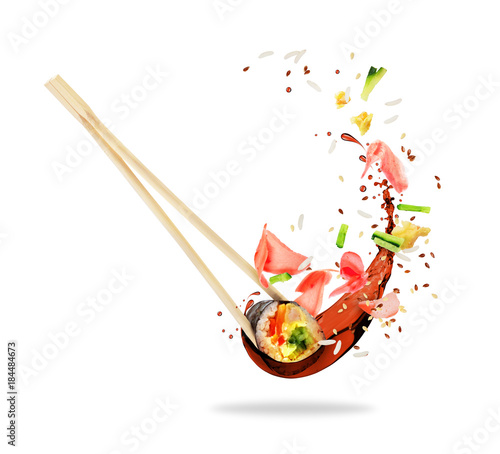 Tuinposter Sushi bar Piece of sushi sandwiched between chopsticks with splashes of soy sauce, isolated on white background