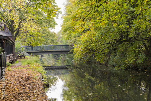 Autumn scene brilliant of fall color reflecting in small pond with bridge arching over water