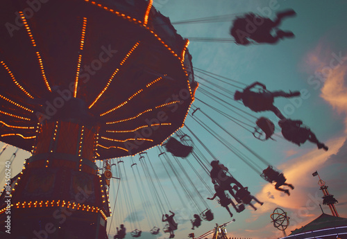 Keuken foto achterwand Amusementspark local fair at dusk with people riding swinging rides and enjoying the summer atmosphere toned with a retro vintage instagram filter app or action