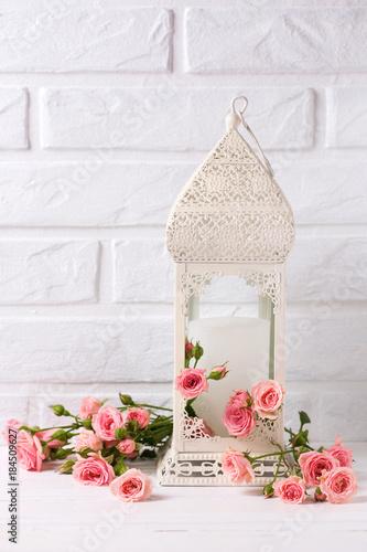 Foto op Plexiglas Magnolia Tender pink roses flowers and decorative white lantern against white brick wall.