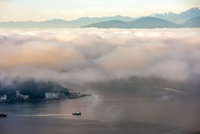 A Foggy Morning In Seattle Over Puget Sound With A Boat Below And The Olympic Mountains Above