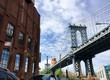 Building and Manhattan bridge with cloudy sky