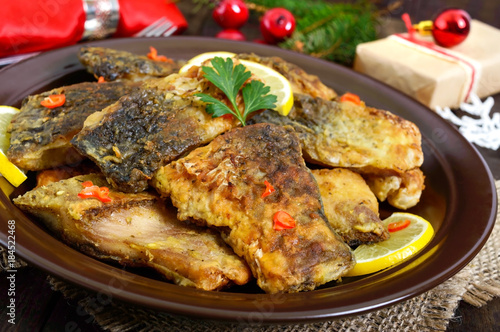 Fototapety, obrazy: Pieces of fried fish (carp) on a ceramic plate on a dark wooden background.