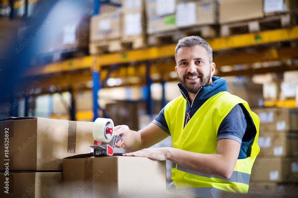 Fototapeta Male warehouse worker sealing cardboard boxes.