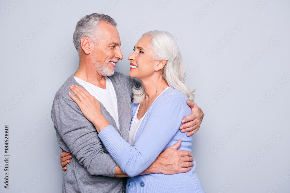 Fototapety, obrazy: Portrait of lovely adorable cute happy senior couple, they are hugging, smiling and looking at each other, isolated on grey background