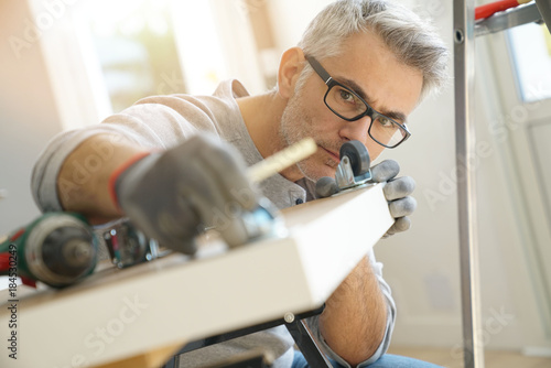Man at home assembling DIY furniture Canvas Print