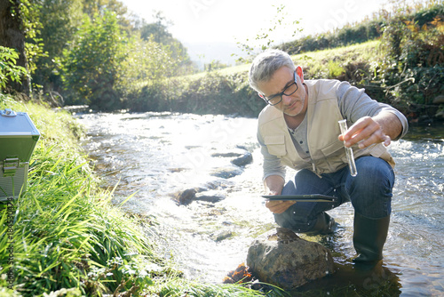 Biologist testing water quality of river Wallpaper Mural