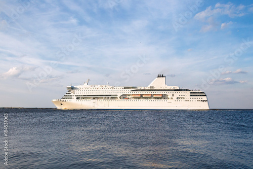 The ferry of white color floats down the river in sunny day against the background of the blue sky and clouds Fototapete