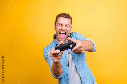 Fotografie, Obraz  Portrait of young, cheerful, attractive, very excited guy holding joystick and p